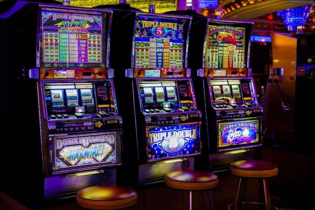 Drei Spielautomaten, nebeneinander aufgestellt, mit Barhockern